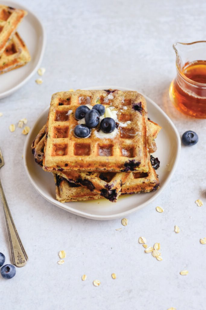 Zucchini Blueberry Oat Waffles on plate with fork and syrup